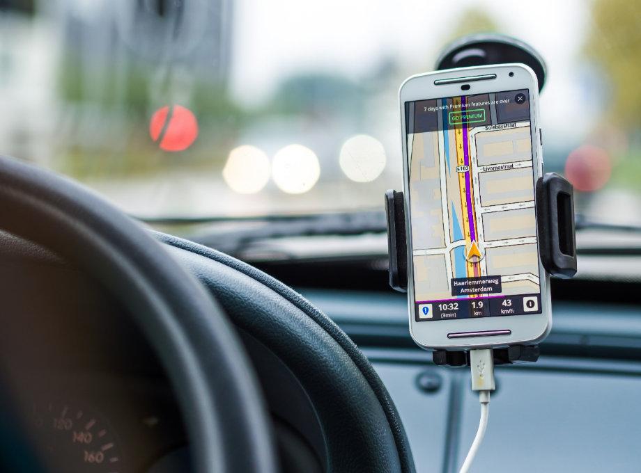 Teléfono celular colocado en un soporte adherido a la parte interior del parabrisas de un vehículo.