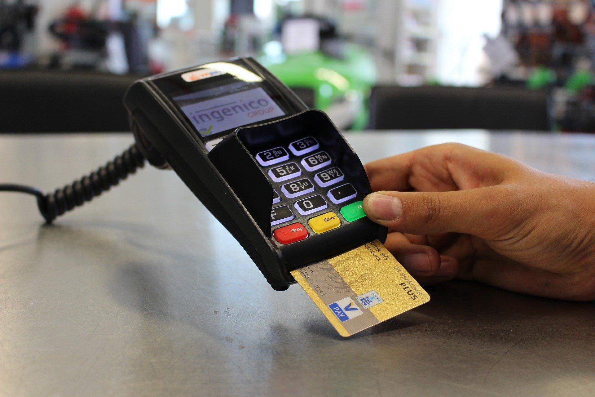 Mano derecha sosteniendo un dispositivo Posnet con una tarjeta inserta en él.