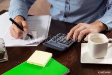 Vista desde arriba de hombre con calculadora, cuaderno y taza de café sobre escritorio de madera